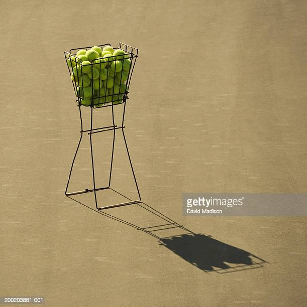 Ball hopper full of tennis balls, shadow on court
