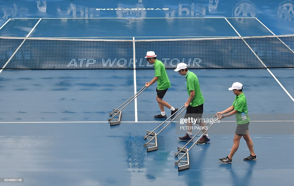TOPSHOT Ball kids dry the court after heavy rain delayed play during the Sydney International tennis tournament in Sydney on January 14 2016 AFP...