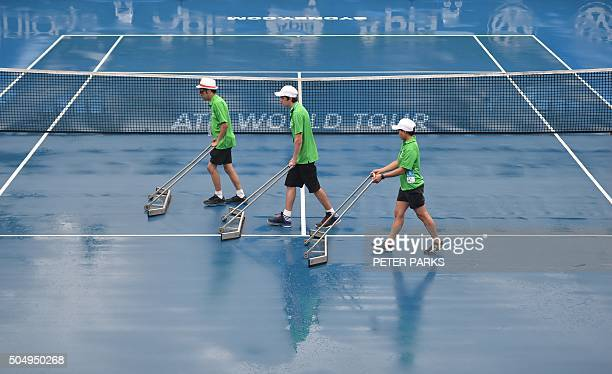 Ball kids dry the court after heavy rain delayed play during the Sydney International tennis tournament in Sydney on January 14 2016 AFP PHOTO /...
