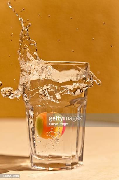 Ball splashing falls into glass of water