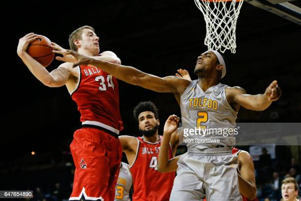 Ball State Cardinals guard Sean Sellers grabs a rebound over Toledo Rockets forward Taylor Adway during a regular season basketball game between the...