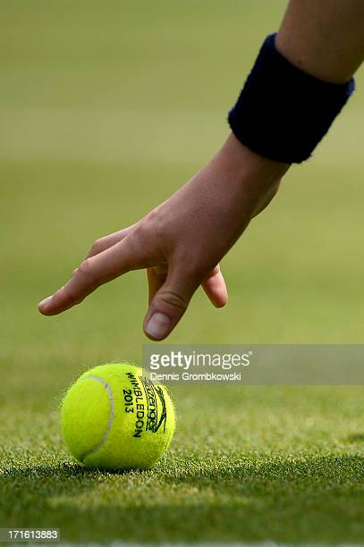 A ballboy collects a tennis ball from the turf during the Ladies' Singles second round match between Petra Martic of Croatia and Karolina Pliskova of...