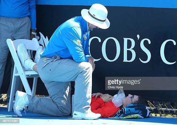 A ballboy faints in the heat as Melbourne heads towards 43 degrees celsius during day two of the 2014 Australian Open at Melbourne Park on January 14...
