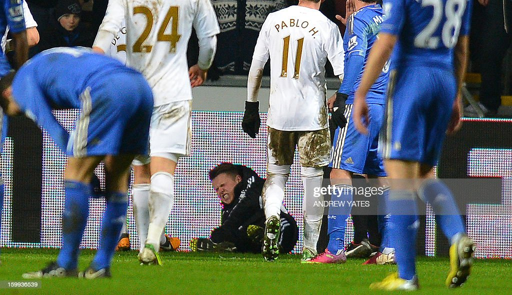 """A ballboy (C) lies on the grounf and reacts after a altercation with Chelsea's Belgium midfielder Eden Hazard during the English League Cup semi-final second leg football match between Swansea City and Chelsea at The Liberty stadium in Cardiff, south Wales on January 23, 2013. After the incident Hazard was sent off by referee Chris Foy. USE. No use with unauthorized audio, video, data, fixture lists, club/league logos or """"live"""" services. Online in-match use limited to 45 images, no video emulation. No use in betting, games or single club/league/player publications."""