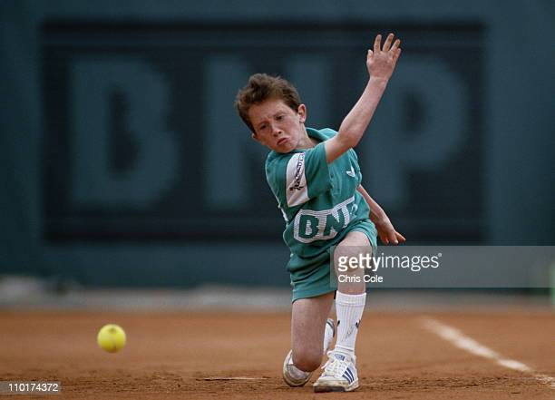 A ballboy passes down a tennis ball along the court at the French Open Tennis Championship on 1st June 1987 at the Stade Roland Garros Stadium in...