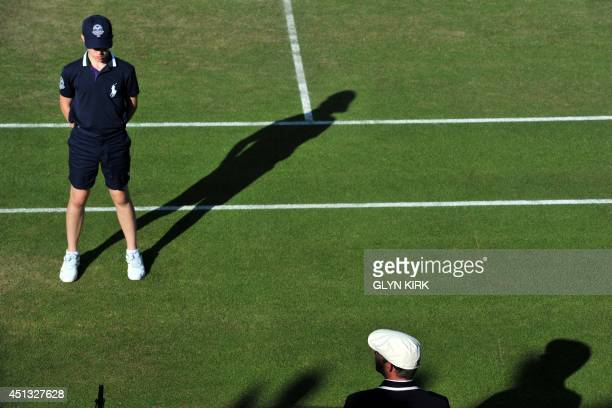 A ballboy stands ready on a court on day five of the 2014 Wimbledon Championships at The All England Tennis Club in Wimbledon southwest London on...