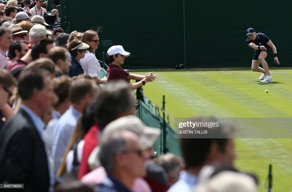 A ballboy throws a ball on the fourth day of the 2016 Wimbledon Championships at The All England Lawn Tennis Club in Wimbledon, southwest London, on June 30, 2016. / AFP / JUSTIN