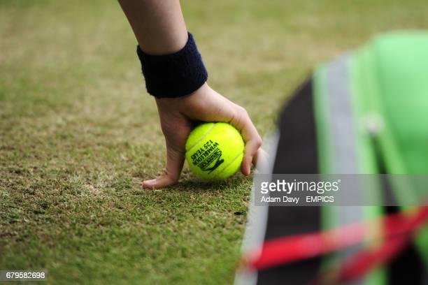 A ballboy with an official Wimbledon matchball in hand