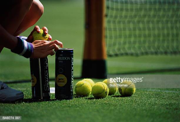 Ballboy with tennis-balls,crouched beside net at sideline,Wimbledon