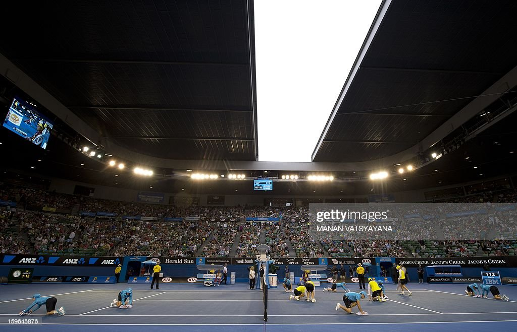 Ballboys and girls dry the court during a rain delay in a women's singles match between Germany's Angelique Kerber and Madison Keys of the US on day five of the Australian Open tennis tournament in Melbourne on January 18, 2013. AFP PHOTO / MANAN VATSYAYANA IMAGE STRICTLY RESTRICTED TO EDITORIAL USE - STRICTLY NO COMMERCIAL USE