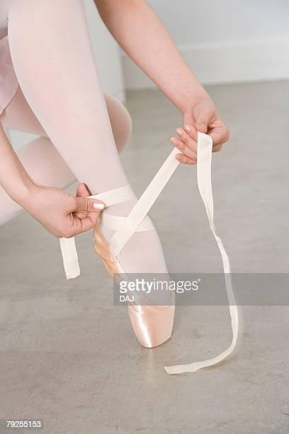 Ballerina adjusting ballet slipper