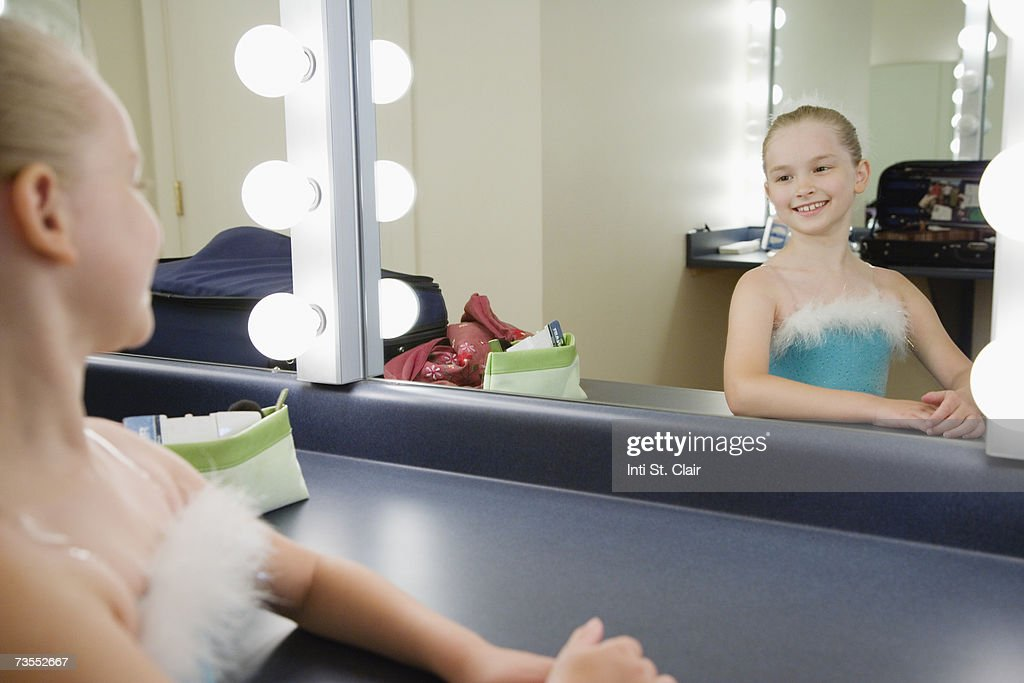 Ballerina (8-9) booking at herself in dressing room mirror, smiling : Stock Photo