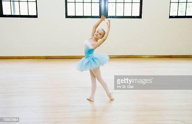 Ballerina  (8-9) dancing in studio, smiling