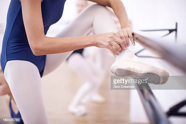 Ballerina fastening ballet slipper at the barre
