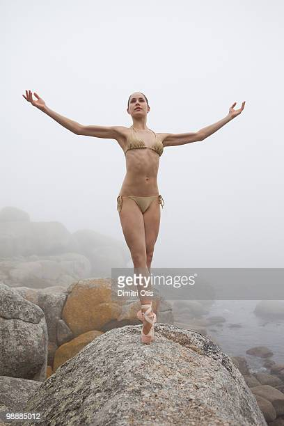 Ballerina in bikini posing on rocks