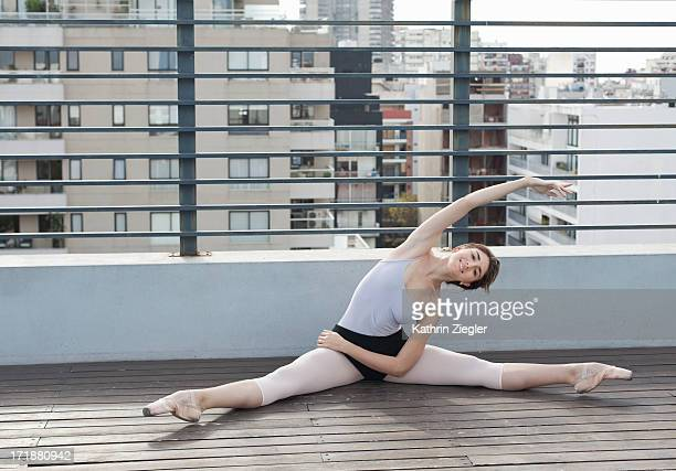 ballerina in pointe shoes stretching on sun deck