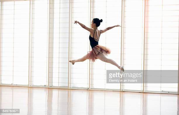 Ballerina in studio mid jump