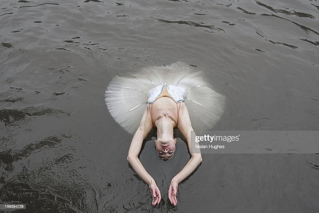 Ballerina in tutu performing on water : Stock Photo