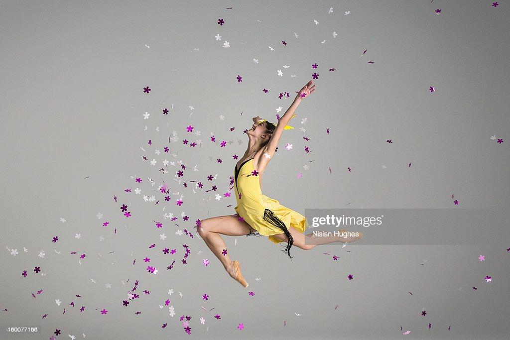 Ballerina jumping through purple flowers : Stock Photo