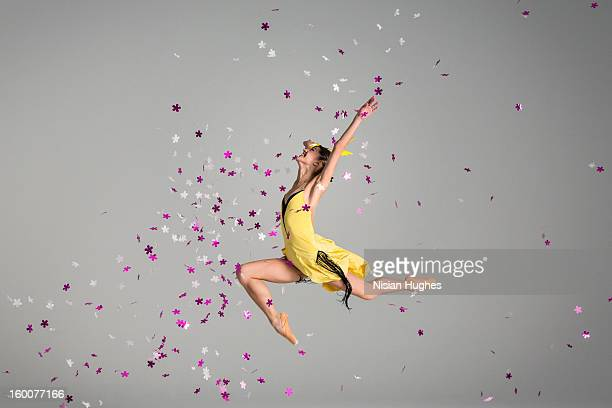 Ballerina jumping through purple flowers