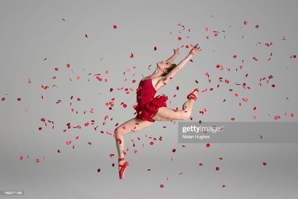 Ballerina jumping through red flowers petals