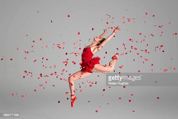 Ballerina jumping through red flowers petals