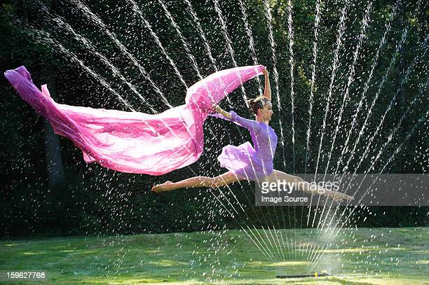 Ballerina leaping over water sprinkler with fabric