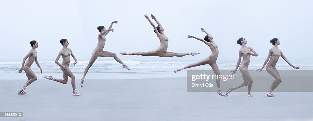 Ballerina leaping through air on beach