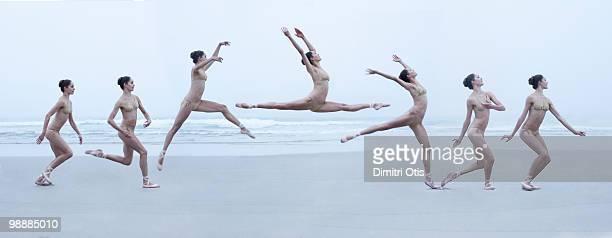 Ballerina leaping through air on beach