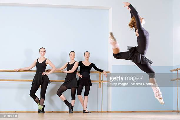 A ballerina leaping through the air as three other women look on