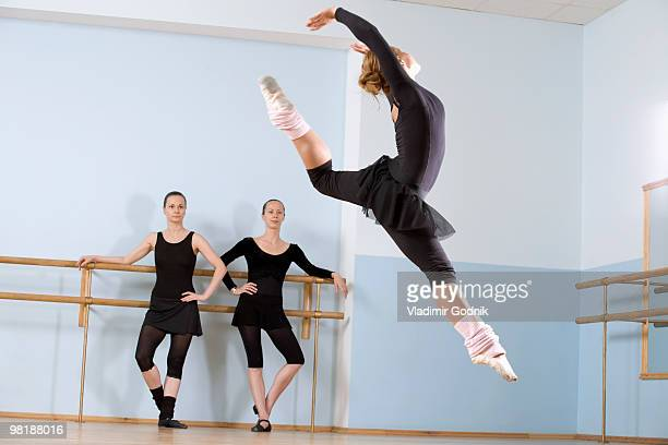 A ballerina leaping through the air as two other women look on