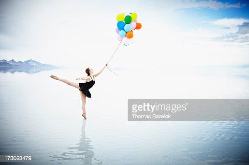 Ballerina on tip toe in water holding balloons