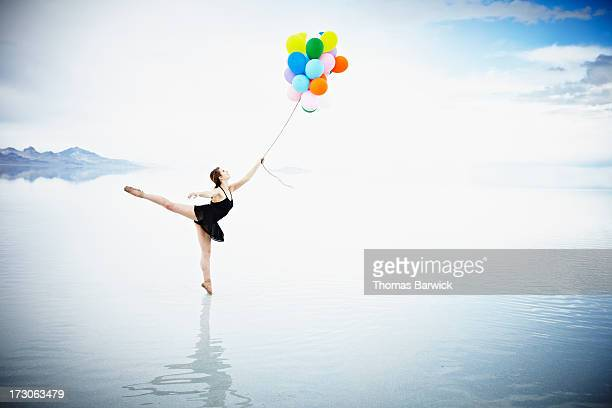 Ballerina on tip toe in water holding balloons