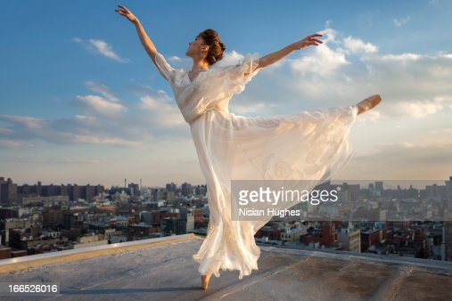 Ballerina performing Arabesque on roof : Stock Photo