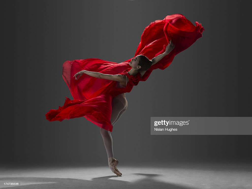 ballerina performing on pointe in red silk dress