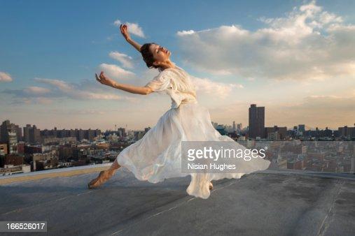 Ballerina performing Tombé, cambré back on roof : Stock Photo