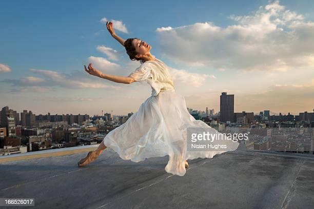 Ballerina performing Tombé, cambré back on roof