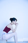 Ballerina sitting on chair in studio, closing eyes, toned image