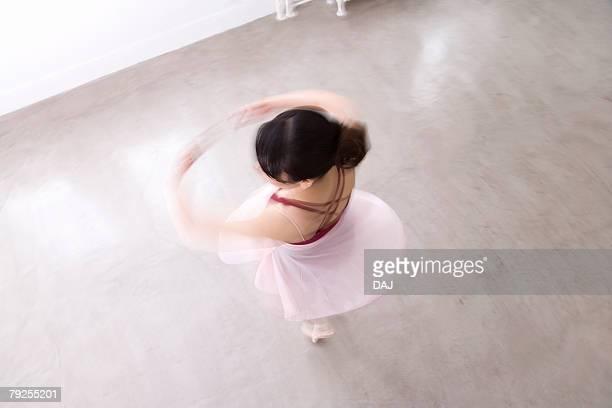 Ballerina spinning on floor, blurred motion
