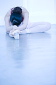 Ballerina stretching on floor, copy space, toned image