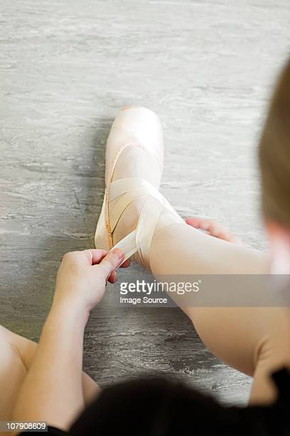 Ballerina tying ribbon on slipper
