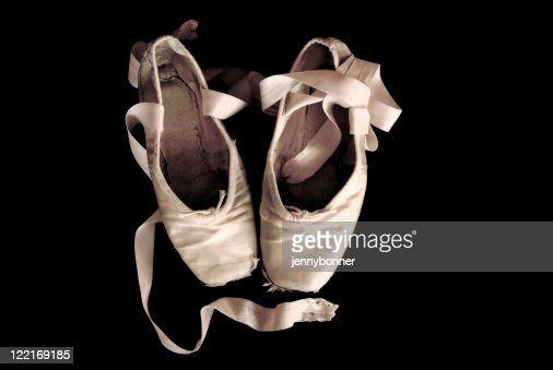 ballerina worn out ballet pointe shoes black background