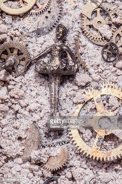 Ballet dancer and gears on sand