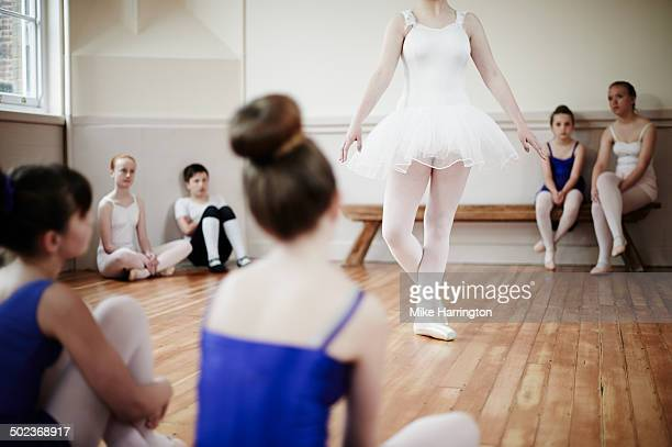 Ballet dancer demonstrating dance pose to class