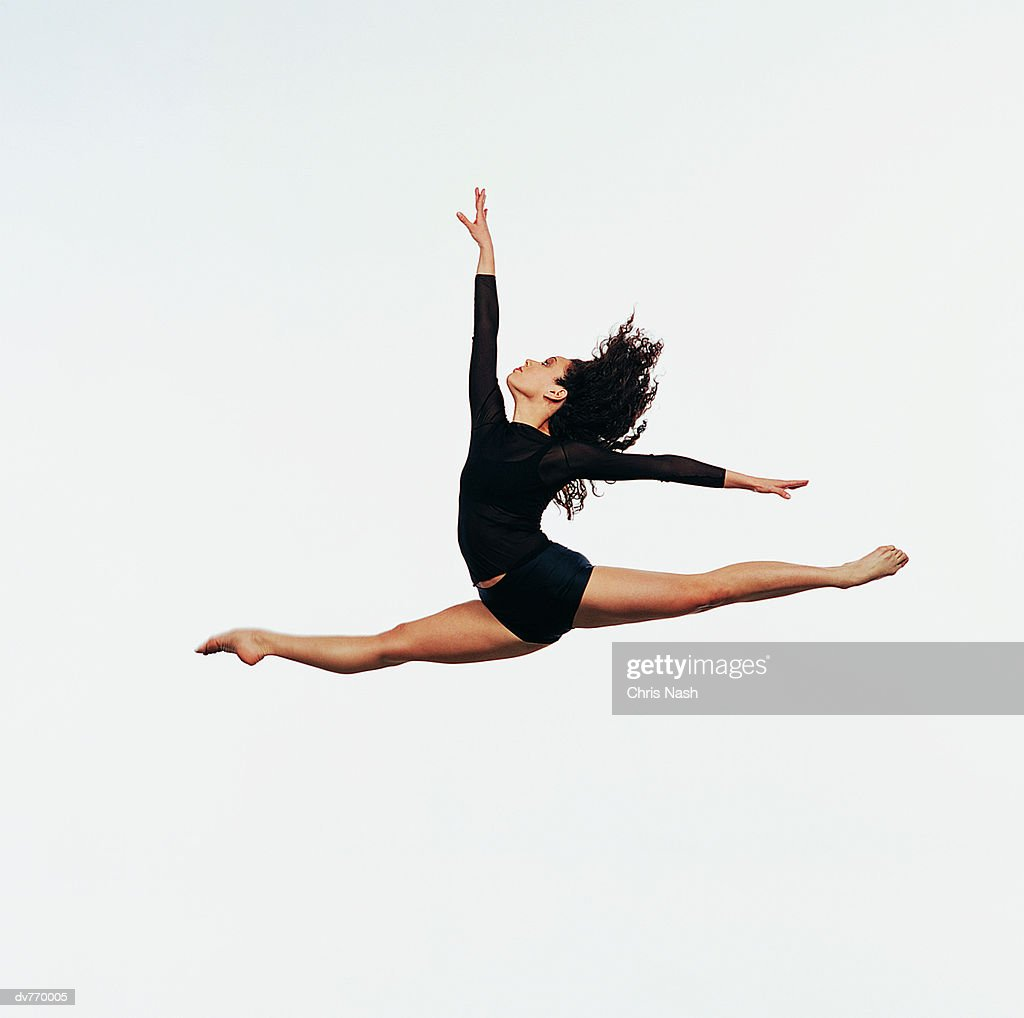Ballet Dancer Doing the Splits in Mid Air With One Arm Raised : Stock Photo