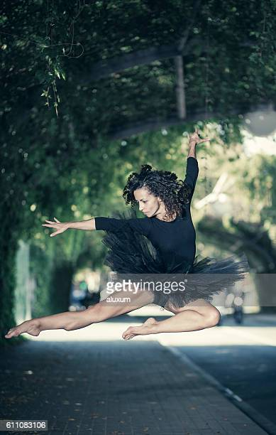 Ballet dancer in tutu dress  jumping in the city