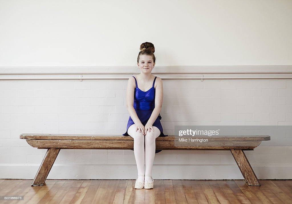 Ballet dancer on bench smiling to camera.