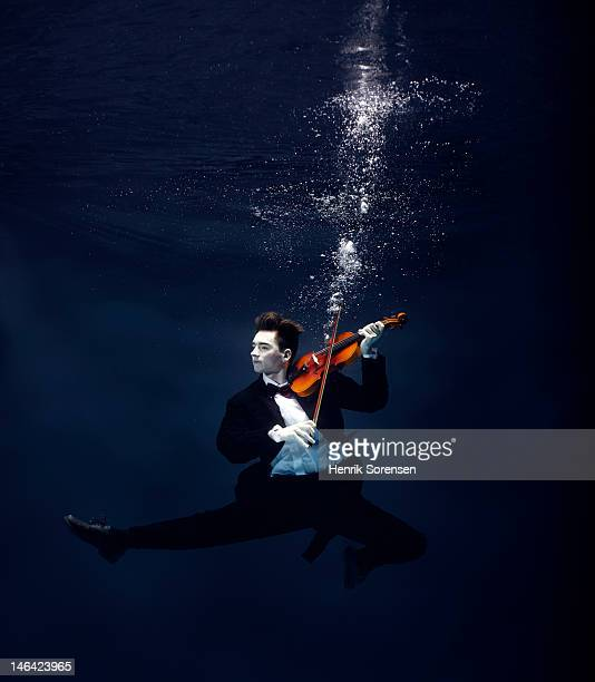 ballet dancer playing violin underwater