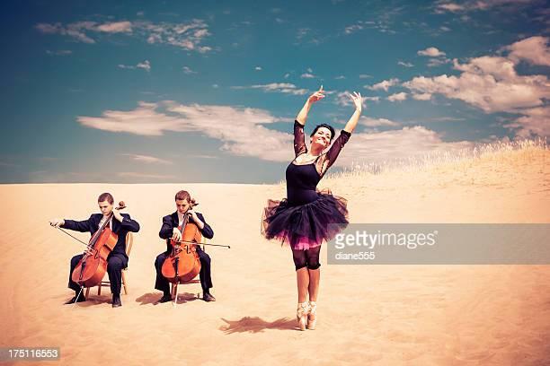 Ballet Dancer Poses En Pointe And Cellist In The Desert