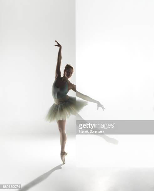 Ballet dancer standing behind a opaque screen